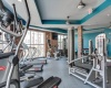 View of the Fitness Center at Alpha Mill Apartments, Showing Cardio Machines, Cable Machines, TV, and Window View
